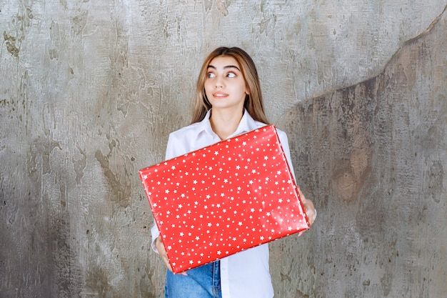 Woman in white shirt holding a red gift box with white dots on it and looks confused and thoughtful.