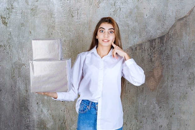 Woman in white shirt holding silver gift boxes and looks confused