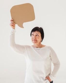 Woman in white shirt holding speech bubble