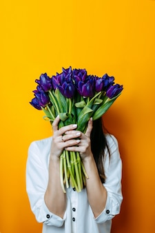 Woman in white shirt holds big bunch of tulips. bunch of purple tulips in womans hands.