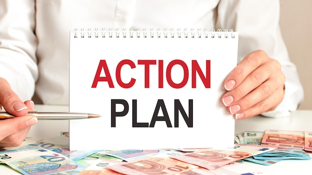 A woman in a white shirt holds a piece of paper with the text: action plan. multicolored markers and tablet on a table. business concept for companies and educational institutions.