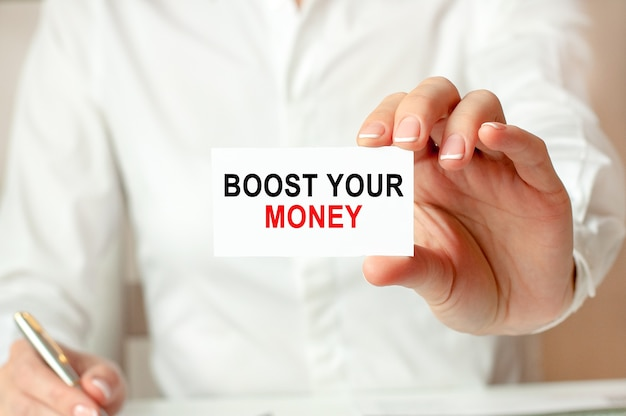A woman in a white shirt holds a piece of paper with the text: boost your money. business concept for companies.