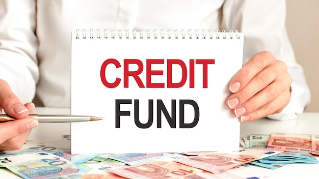 A woman in a white shirt holds a piece of paper with the text: credit fund