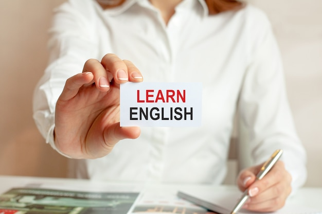 A woman in a white shirt holds a piece of paper with the text: learn english. business concept for companies
