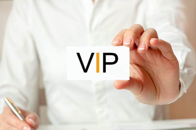 A woman in a white shirt holds a piece of paper with the text: vip. business concept for companies. vip - short for very important person.