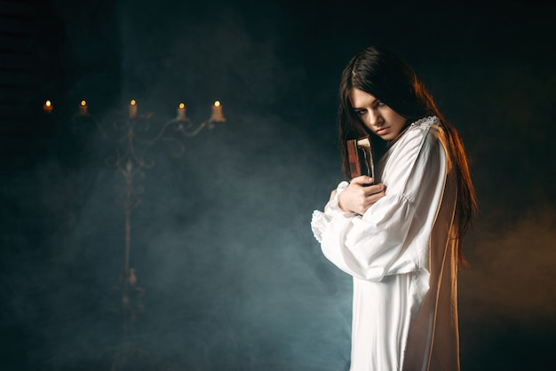 Woman in white shirt holds spellbook in hands, candles and smoke