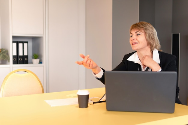 A woman in a white shirt is coaching listeners in the business room