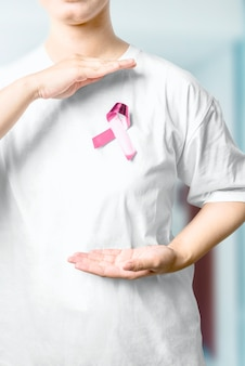 Woman in a white shirt showing pink awareness ribbon in the hospital