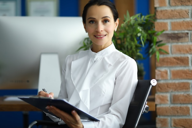Woman in white shirt sits in office and holds clipboard in her hands