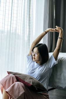 A woman in a white shirt sitting on the bed and raising both arms.
