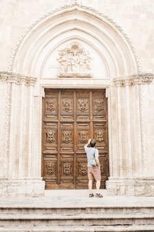 Woman in white shirt standing in front of brown wooden door