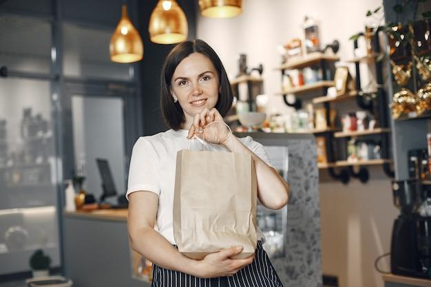 Donna in una camicia bianca al supermercato. bruna guarda la telecamera e sorride.