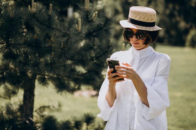 Woman in white shirt using phone in a backyard