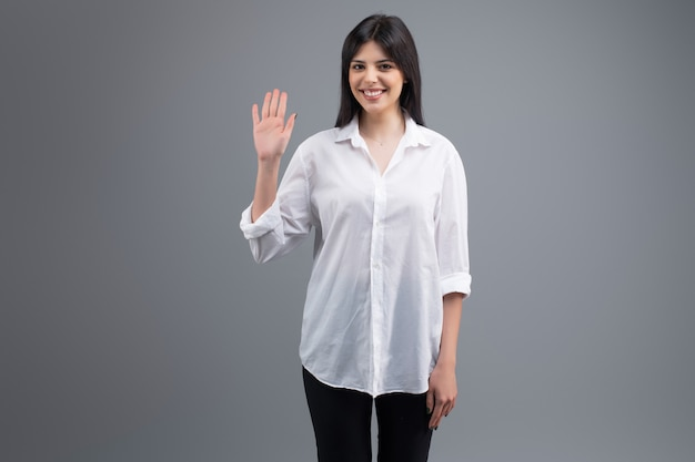 Woman in white shirt wawing hello with palm of hand