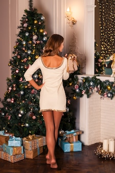 Woman in white shot dress standing near a christmas tree