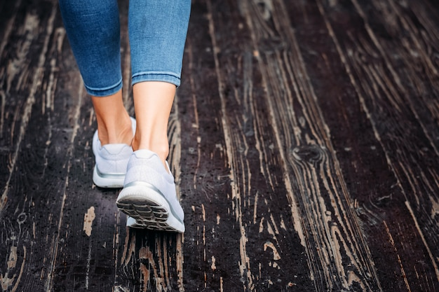 Woman in white sneakers go on the wooden floor