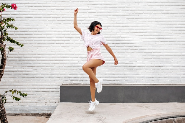 Woman in white sneakers jumping on street. full length view of dancing woman enjoying summer.