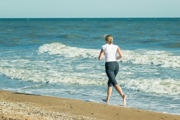 A woman in a white sports jacket is jogging on the beach.