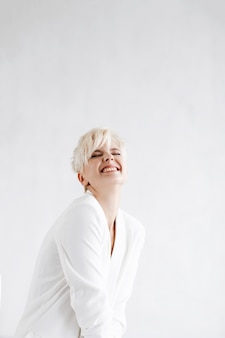 Woman in white suit looks funny posing before a white wall