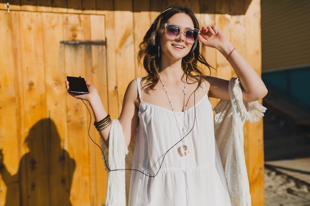 Woman in white summer dress listening to music on headphones dancing and having fun