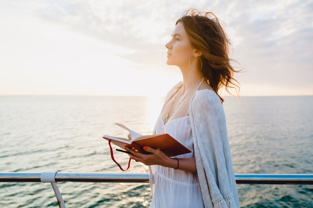 Woman in white summer dress walking by the sea on sunrise with diary book in romantic mood thinking and making notes