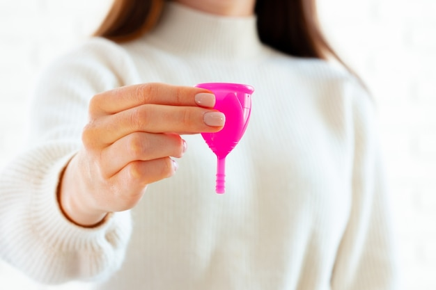 Woman in white sweater holding pink menstrual cup in hands close up photo