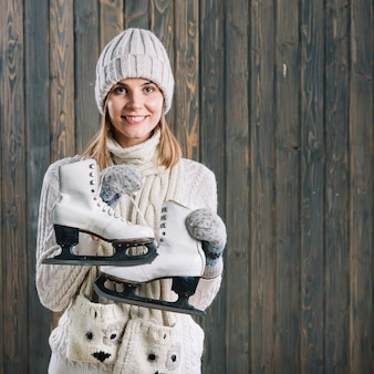 Woman in white sweater holding skates