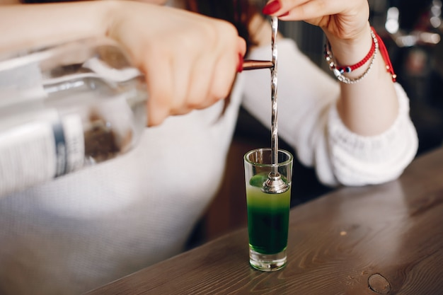Woman in a white sweater pouring green syrop into glass