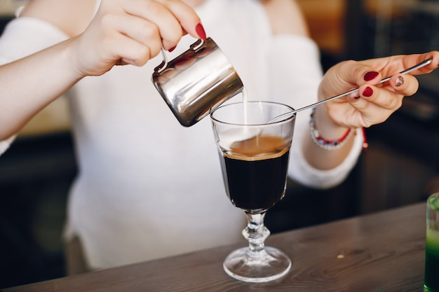 Woman in a white sweater pouring milk into coffee dessert
