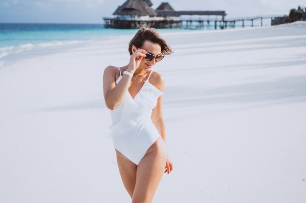 Woman in white swimming suit by the ocean