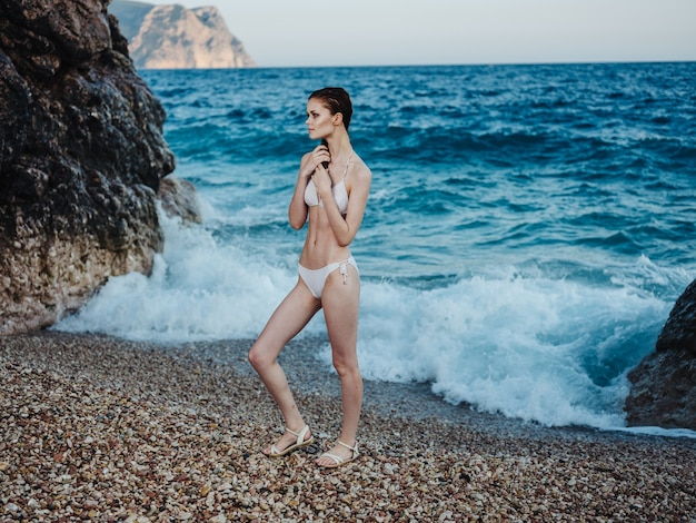 A woman in a white swimsuit in full growth on a rocky beach near the sea, clear water.