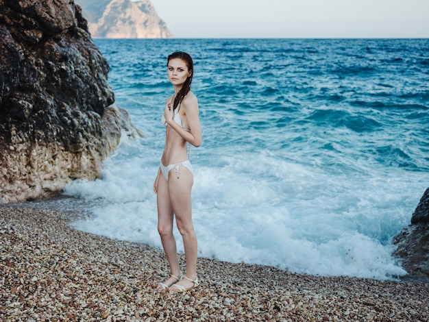 A woman in a white swimsuit in full growth on a rocky beach near the sea, clear water