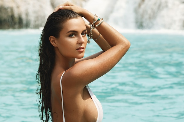 Woman in white swimsuit is posing on the rock beside waterfall