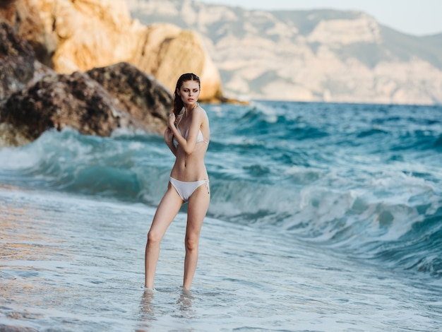 Woman in a white swimsuit but the ocean shore on the beach white foam ocean rocks mountains in the background.