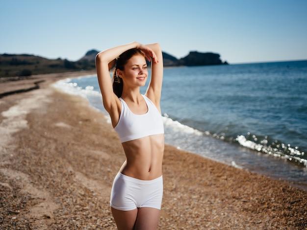 Woman in white swimsuit posing beach shore ocean