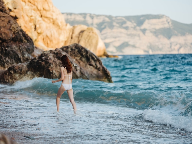 A woman in a white swimsuit walks along the shore of a mountain landscape fresh air. high quality photo