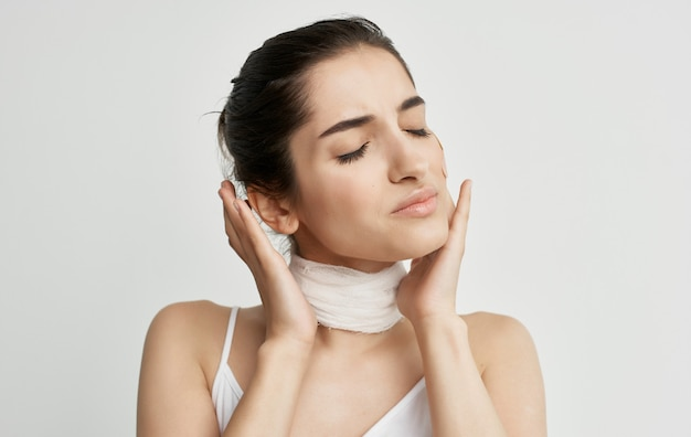 Woman in white t-shirt bandaged neck health problems