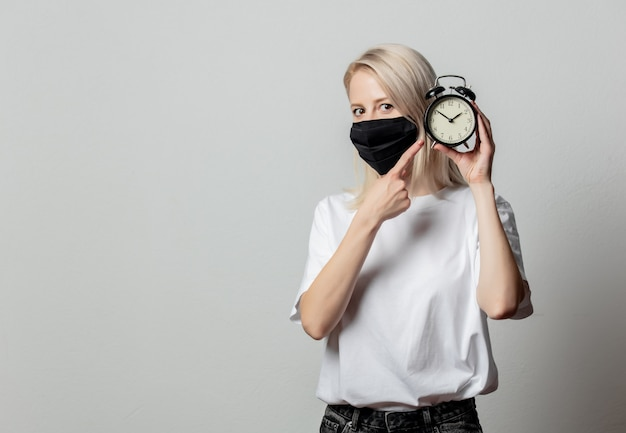 Woman in white t-shirt and black face mask with alarm clock on white wall