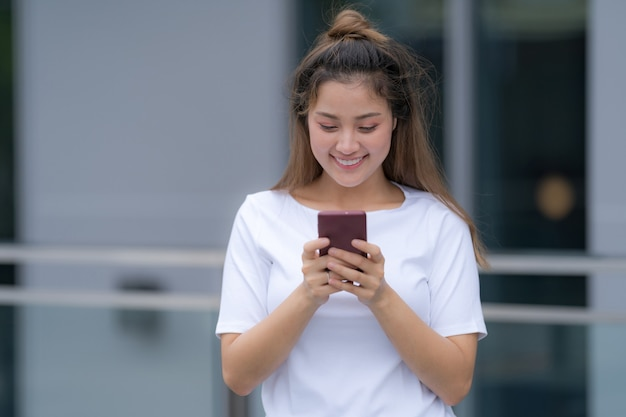 Woman in white t-shirt and blue jeans using phone standing on a floor outside in the city street background
