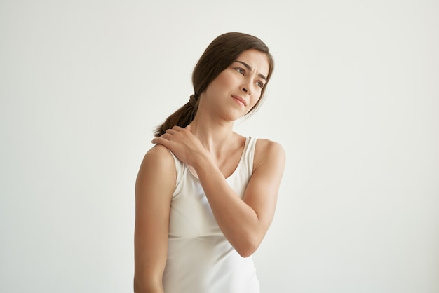 Woman in white t shirt chronic pain health problems compounds. high quality photo