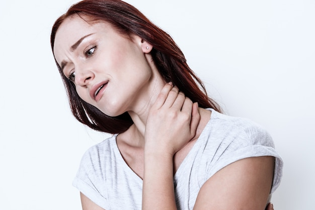 Woman in white t-shirt has a sore neck.
