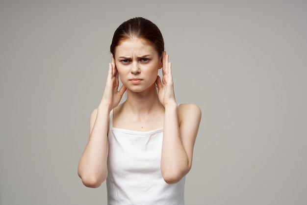 Woman in white t-shirt holding ears discontent migraine health problems
