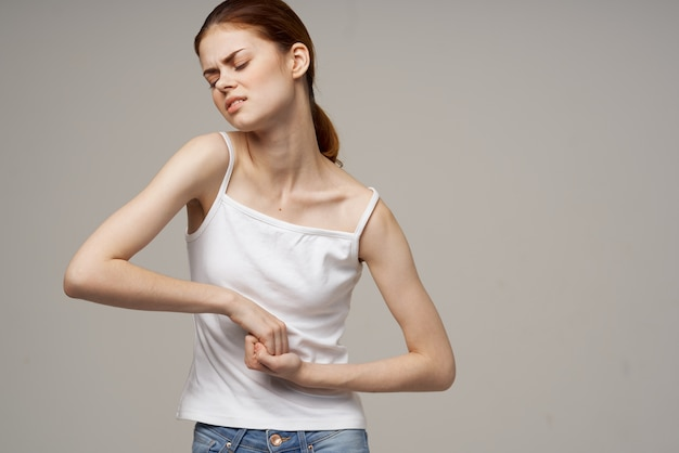 Woman in white t-shirt holding her belly health problems menstruation gynecology