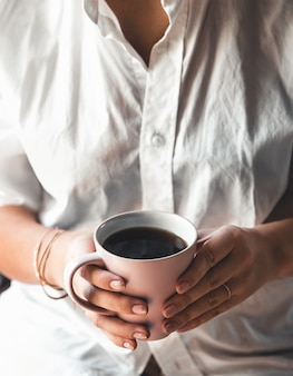 Woman in a white t-shirt holds morning coffee in a pink ceramic cup