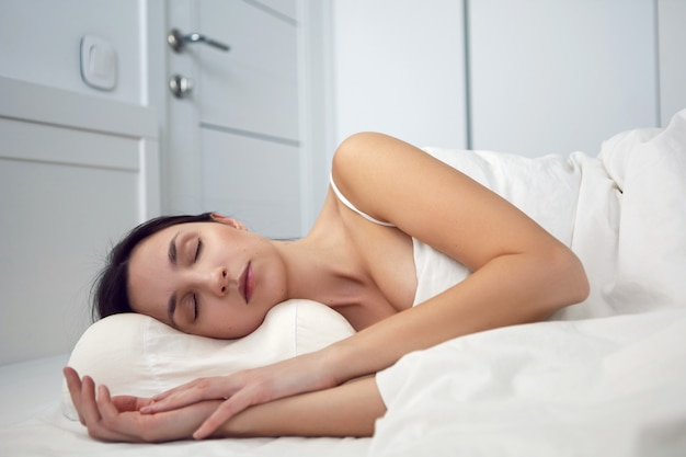 Woman in a white t-shirt is lying on the bed and a pillow is under the blanket in the room
