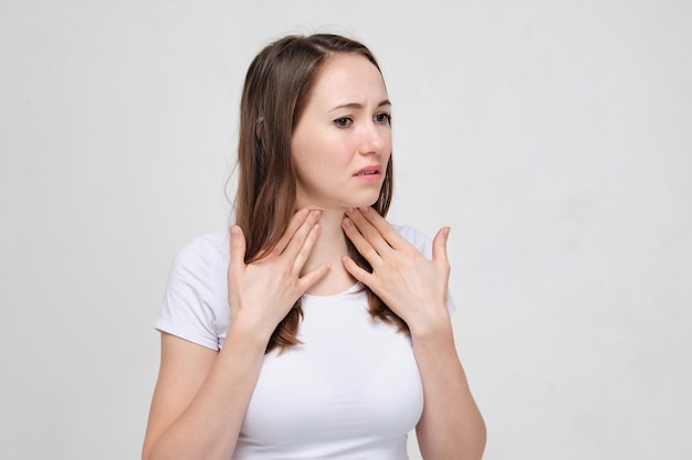 Woman in white t-shirt is massaging her neck because of suspected thyroid problems.