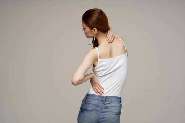 Woman in white t-shirt pain symptoms in the joints arthritis studio treatment. high quality photo