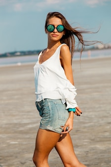 Woman in white t shirt and stylish sunglasses posing on the beach.