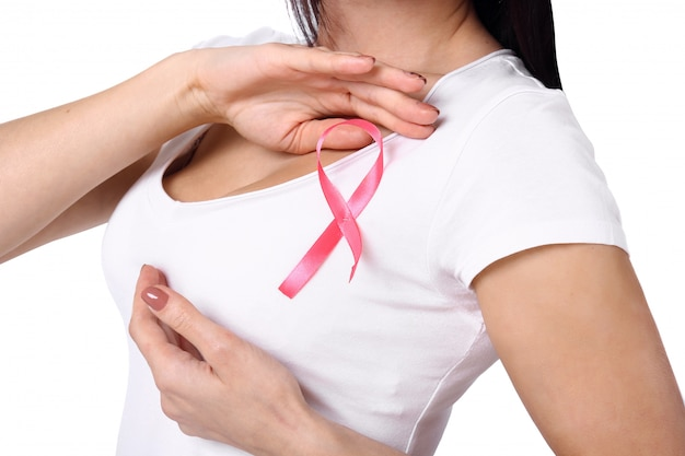 Woman in white t-shirt with pink breast cancer awareness ribbon.