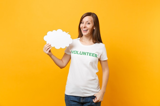 Woman in white t-shirt with written inscription green title volunteer hold empty blank say cloud speech bubble isolated on yellow background. voluntary free assistance help charity grace work concept.